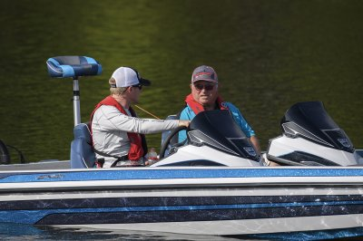 two anglers talking about fishing in a dual console fx20